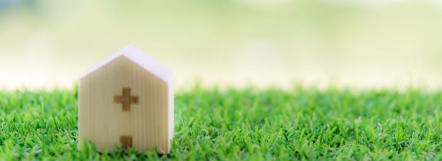 緑の芝生に置かれた木製の病院の置物
