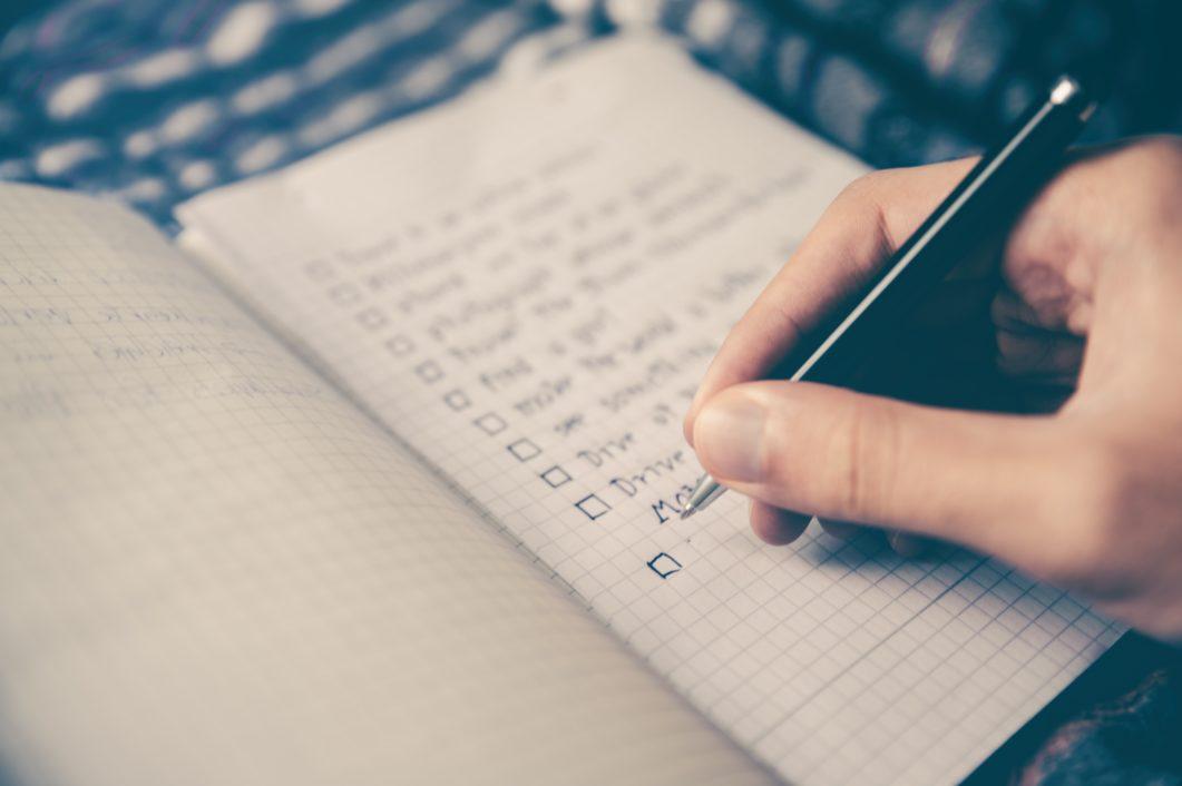 ノートにチェックリストを書いている手元の写真